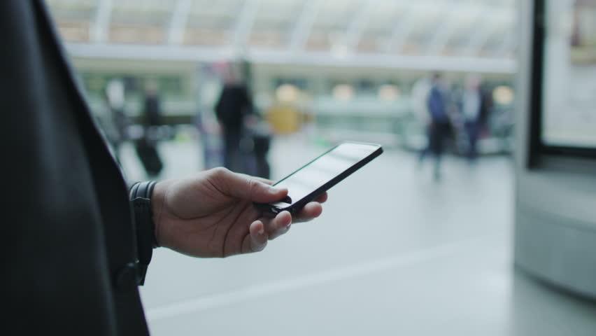 Businessman looking at his phone as he walks...