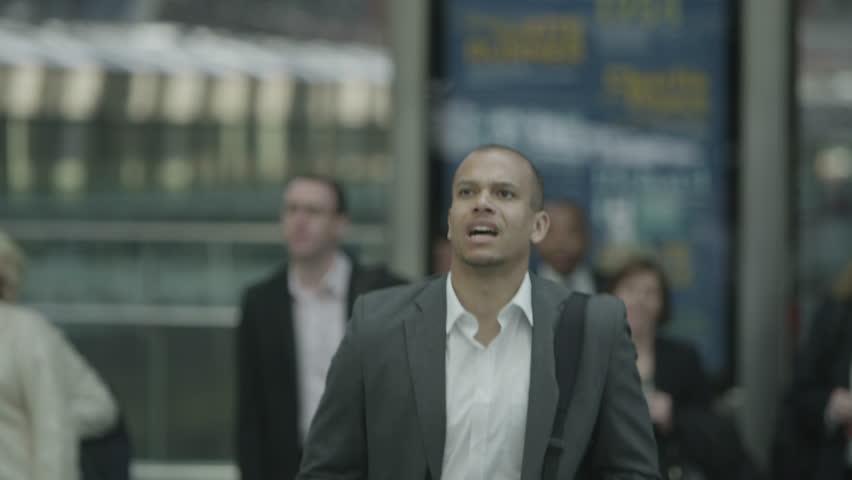 Stressed businessman at railway station runs to...