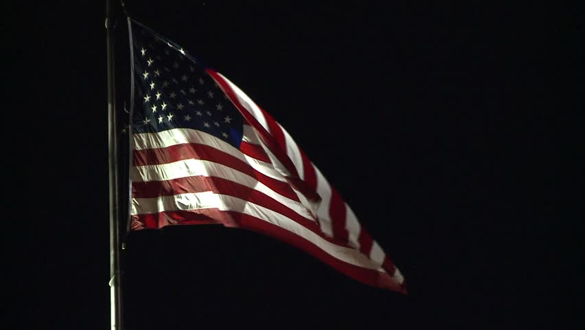 AMERICAN FLAG USA DRAMATIC LITE WAVING NIGHT MEDIUM SHOT IN WIND LONG CLIP HD STOCK VIDEO CLIP FOOTAGE 1920X1080 HIGH DEFINITION 1080