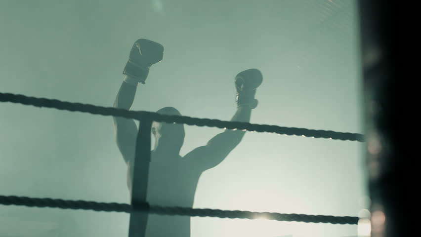 Male Boxer lifts his arms and parades the ring victorious from the fight.