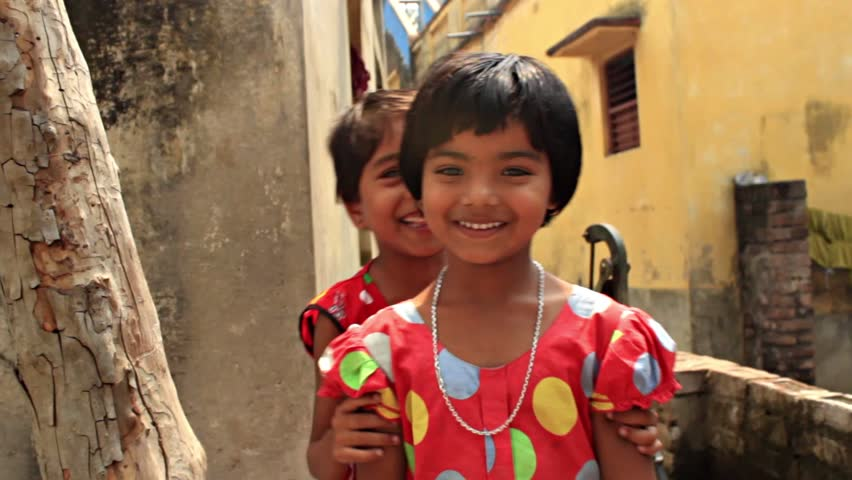 Two cute and sweet sisters playfully pose for the camera. HD 1920 by 1080. Filmed in Navadvipa, Nadia, Bengal, India.