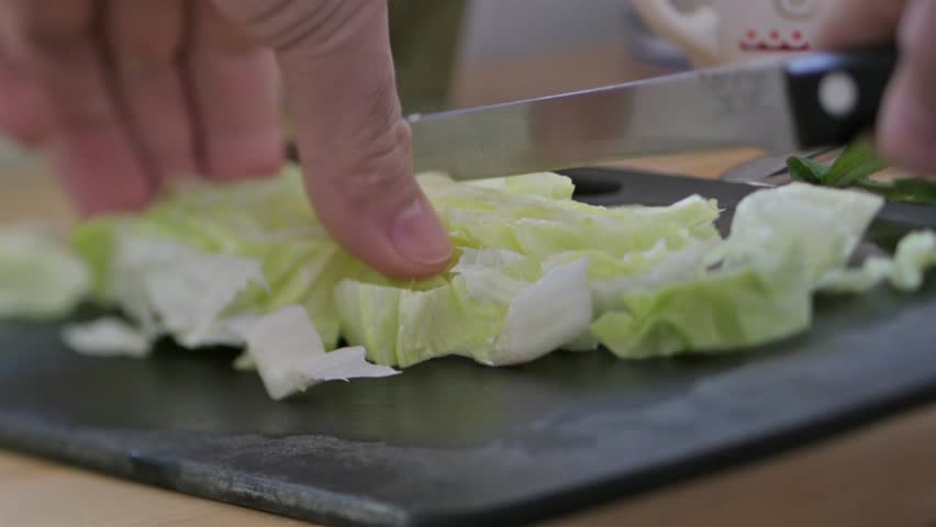 close-up of chef hands slicing fresh parsley on wooden kitchen