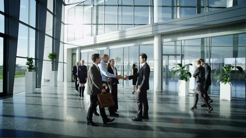Business people meet and shake hands in large modern office building | Shutterstock HD Video #6284795