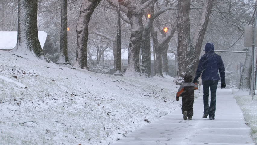 Young child and mother bundled up in winter gear, walk in snow storm in