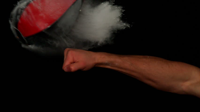 Hand punching maize bag on black background in slow motion