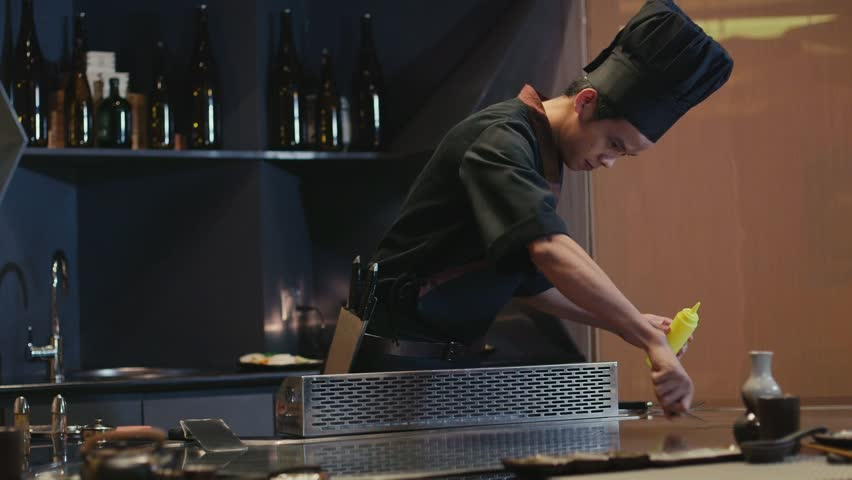 Asian restaurant kitchen, chef cooking food, young man as professional cook working, preparing vegetables on stove with show, fire, flames. Woman, client, customer choosing from menu list. 14of27