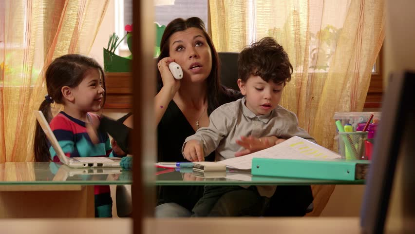 Multitasking mom working at home with children, busy with daughter and son, talking on telephone. Woman, family stress, parenting, motherhood. Businesswoman, manager at work in office, telework. 7of15
