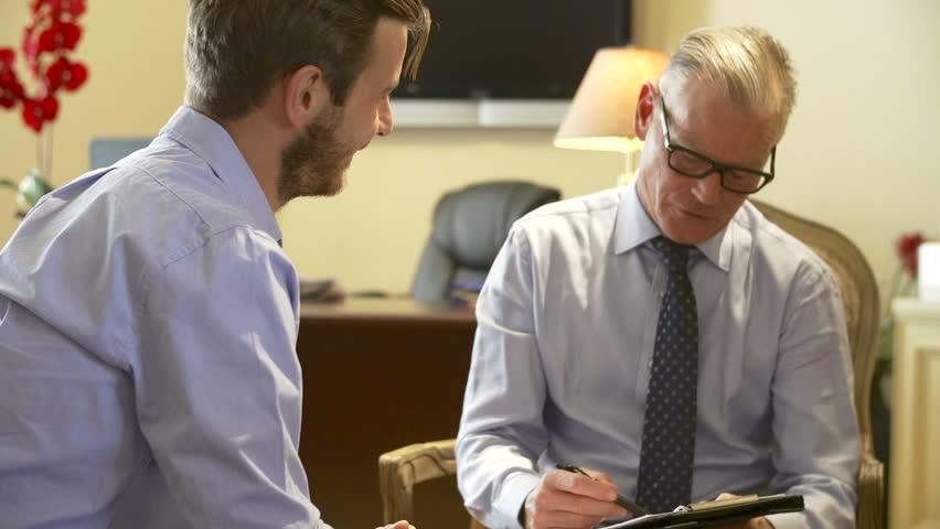 Man Talking To Financial Advisor In Office