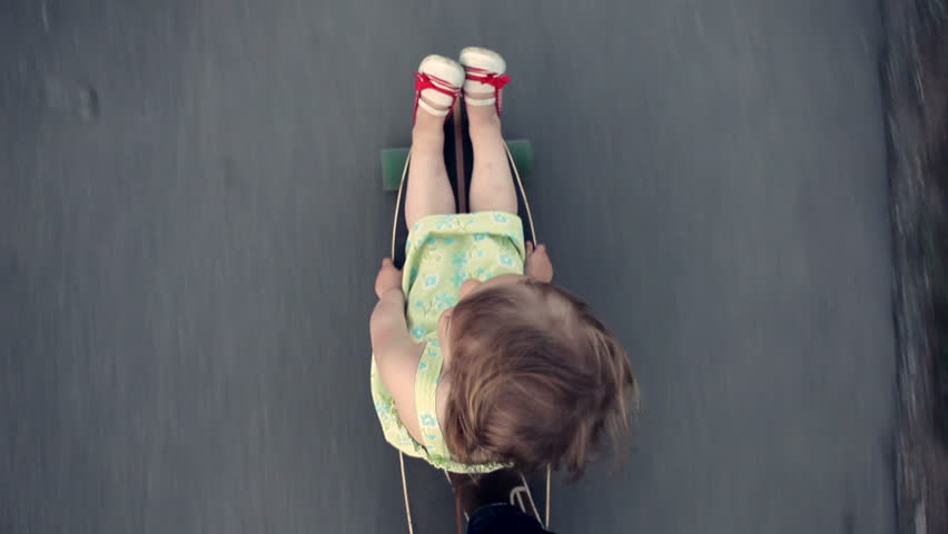 Little girl sits on a longboard, which is run by her dad. View from above.