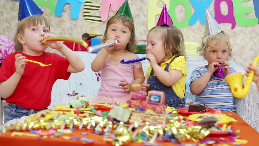 Seven Little Kids Sit At Red Table With Cake And Throw