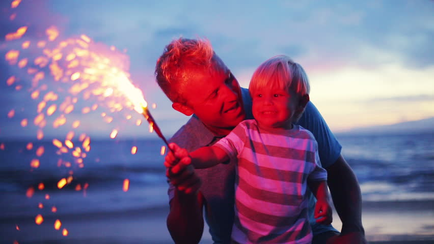 Father and son lighting sparklers on the beach at sunset