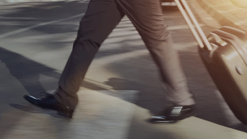 Steadicam shot of African American business man with laptop bag while commuting to work or airport as he walks in a modern city street at sunrise.  | Shutterstock HD Video #6845416