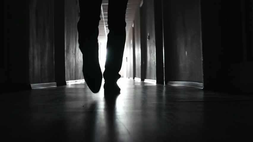 Shaky camera following footsteps of unrecognizable man going along the walkway in the dark