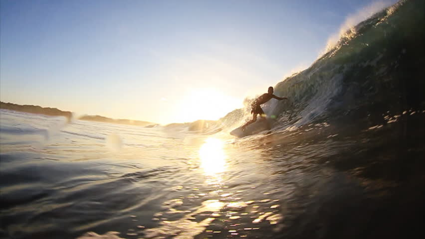 A surfer riding a wave, goes under as the wave breaks, close-up