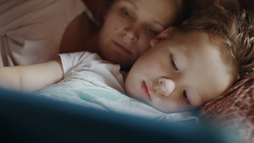Close-up shot of mother and son in bed. Boy playing game on pad, mother helping him with advice. Bedtime entertainment | Shutterstock HD Video #6931624