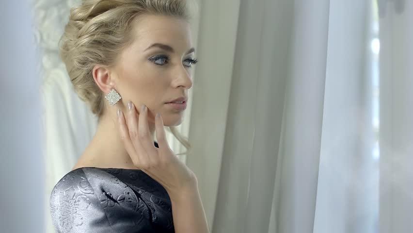 Portrait of beautiful blonde woman with beautiful make-up and elegant hairstyle, close up of beautiful woman wearing shiny diamond earrings #6957193