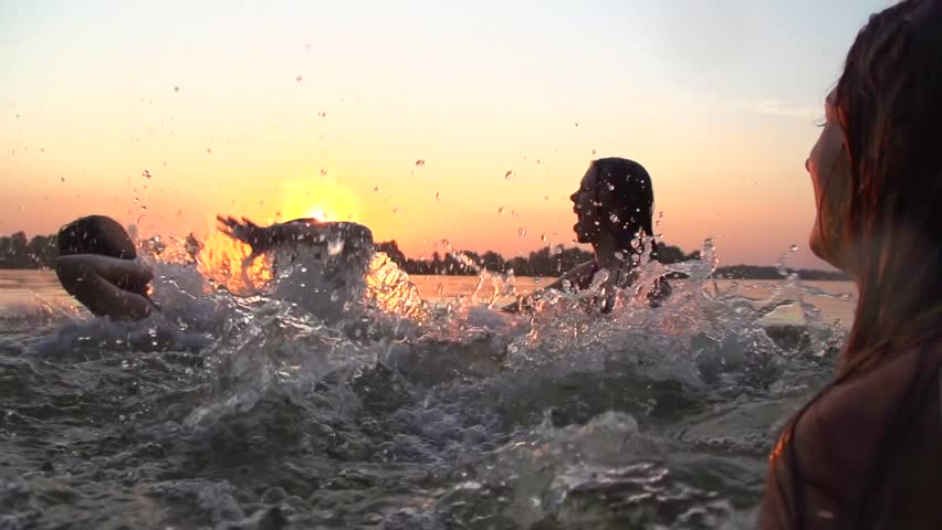 Group of happy teen girls playing in water at the beach on sunset. Beauty joyful teenager friends having fun, dancing and spraying over summer sunset. Beach party. Sun flare. Slow motion. Summertime