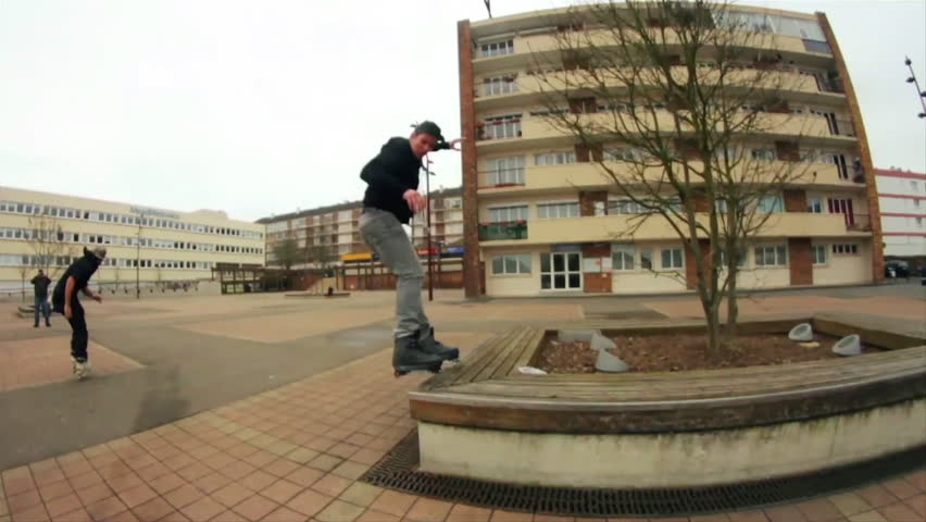 A traceur shows various jumps while running on a pavement, backflip, cartwheel, various skaters visible around him, slow motion