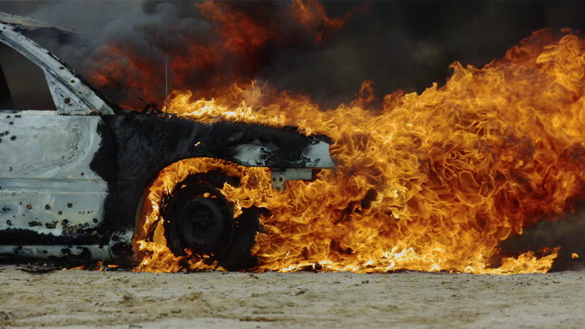 Pan around car on fire.