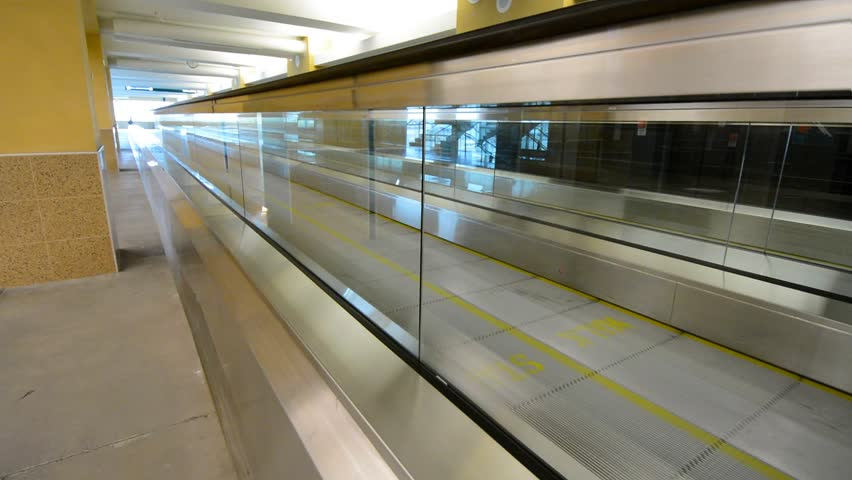 Suburban train rides away from platform at metro station for Electric moving wall pictures