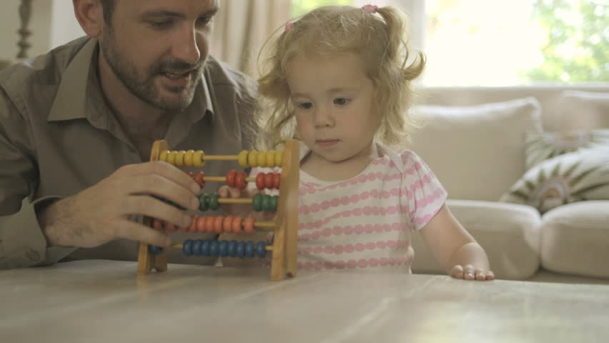 Father assisting his daughter in counting abacus