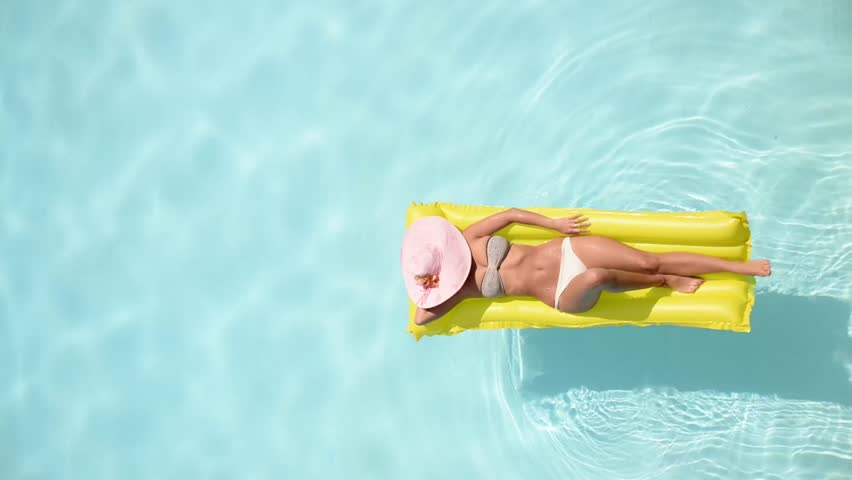 Beautiful young woman relaxing on a yellow inflatable mattress in a swimming pool - Pretty model with perfect shapes chilling out in a exotic resort