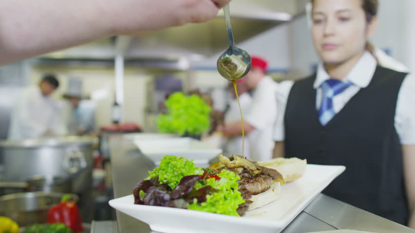 Restaurant Kitchen Video 4k clip. waitress collects her order from the chef in a busy hotel