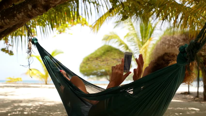 Young Woman with Curly Hair Using Mobile Smart Phone while Relaxing in a Hammock on the Beach. Exotic Island Koh Phangan. Thailand. HD, 1920x1080. | Shutterstock HD Video #7576294