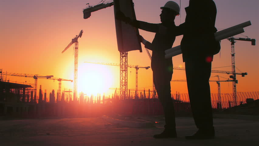 Steadicam shot of skyline and cranes with Asian construction/ executive/ architect/ engineer consultant discussing blue print of new urban development with caucasian construction executive at sunset.