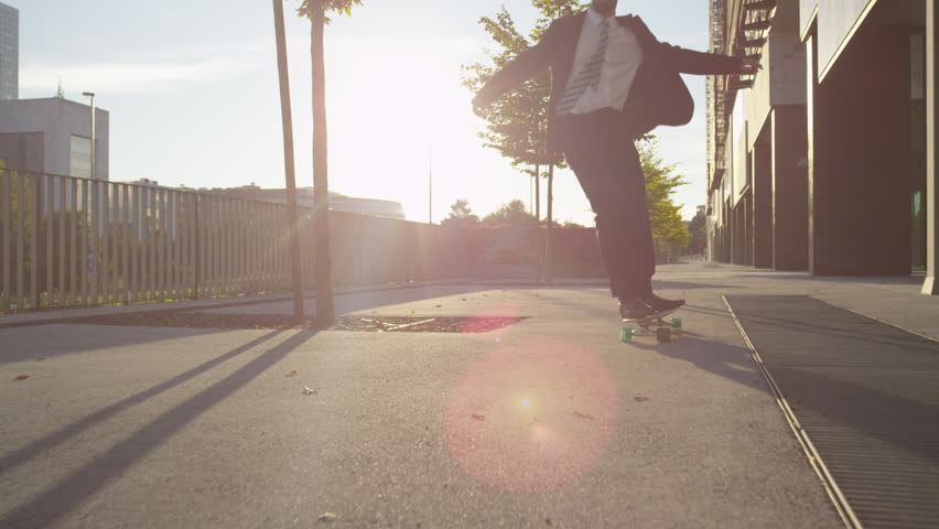 SLOW MOTION: Cool young businessman longboarding to work. Cheerful businessman with arms raised celebrating while skating along the downtown street. Ecstatic businessman skateboarding at golden sunset | Shutterstock Video #7662340