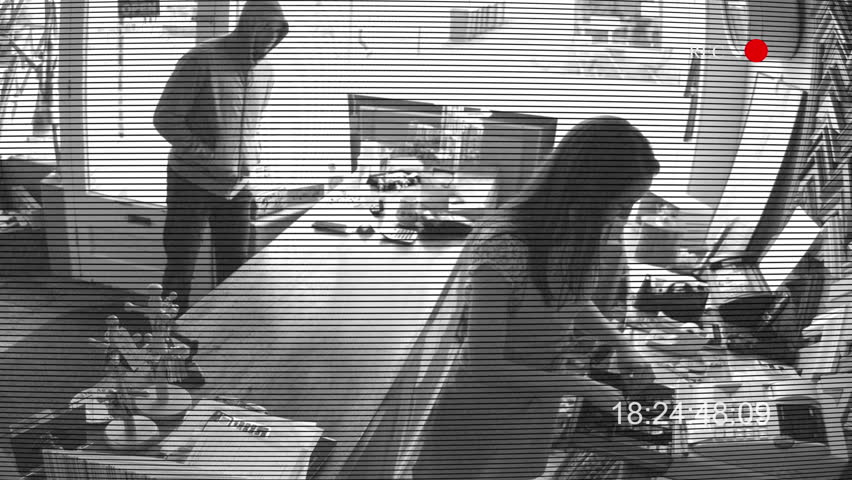 Security camera captures the moment a local store is robbed by a man in hooded clothing. Robber attacks small business and attempts to steal money from the cash register.
