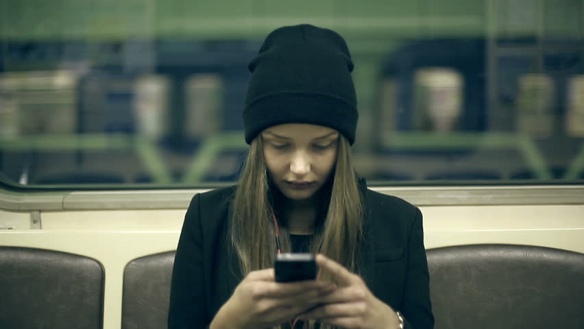 Teen girl rides the subway at night and used smartphone