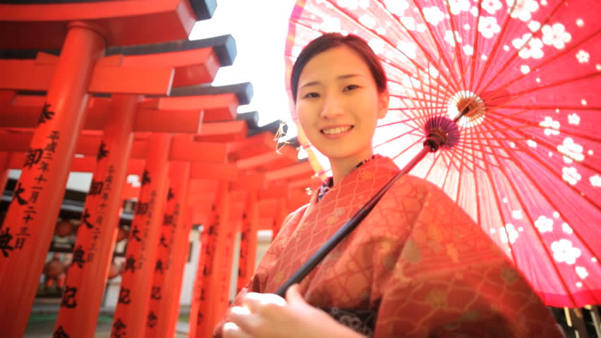 Travel tourism Japan happy young Asian Japanese female traditional red kimono parasol portrait promotional welcome outdoors location
