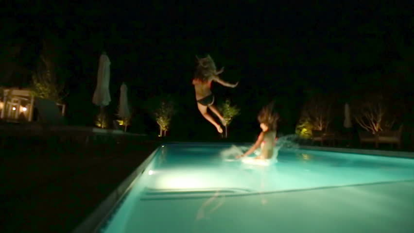 Group Of Teen Girls All Jump Into Deep End Of Swimming Pool At The Same Time Stock -8636