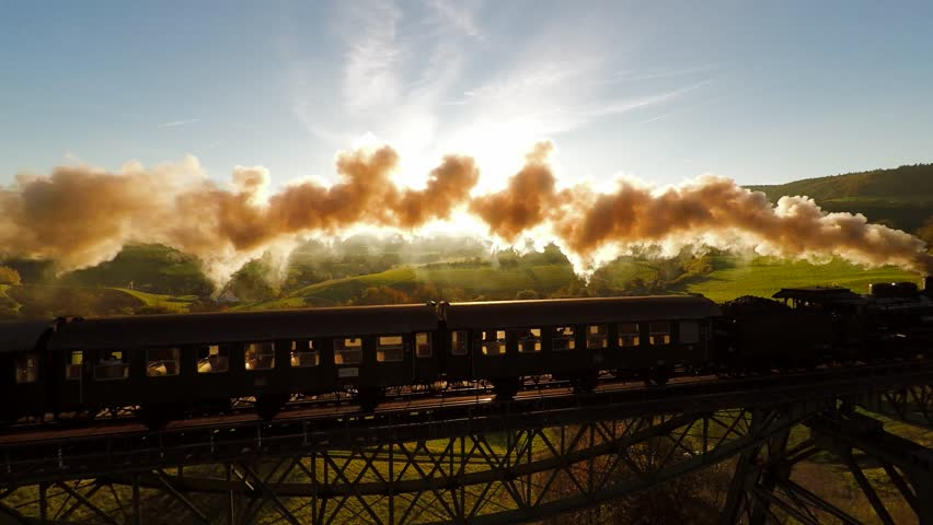 Epic aerial view of steam engine train crossing bridge at sunset magic hour. old locomotive | Shutterstock HD Video #7878088