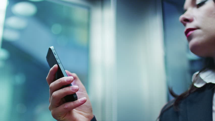 Business Woman in Dark Suit using Mobile Phone in Elevator. Shot on RED Digital Cinema Camera in 4K (ultra-high definition (UHD)), so you can easily crop, rotate and zoom, without losing quality! | Shutterstock HD Video #7886443