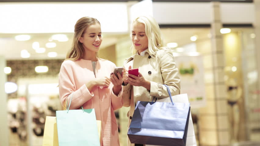 Sale, consumerism, technology and people concept - happy young women with smartphones and shopping bags talking in mall | Shutterstock HD Video #7902118