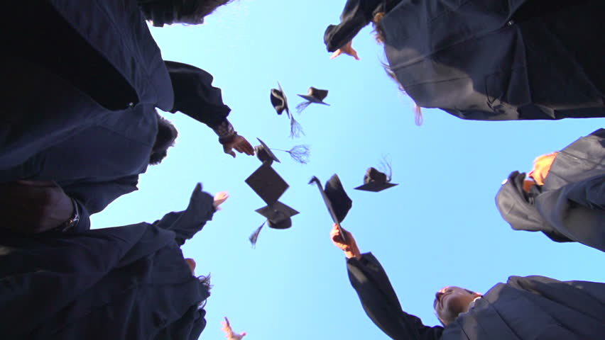 A slow-motion shot from below of a group of racially-diverse students throwing their graduation mortarboards in the air in celebration. | Shutterstock HD Video #7971607