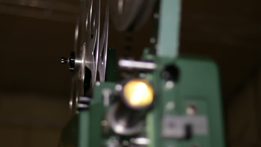 Film Projector Projecting 16mm Movie Rack Focus. A technician projects a 16mm film. 16mm film projection cinema technical footage. Film Technician mounting a 16mm film reel in a film festival.