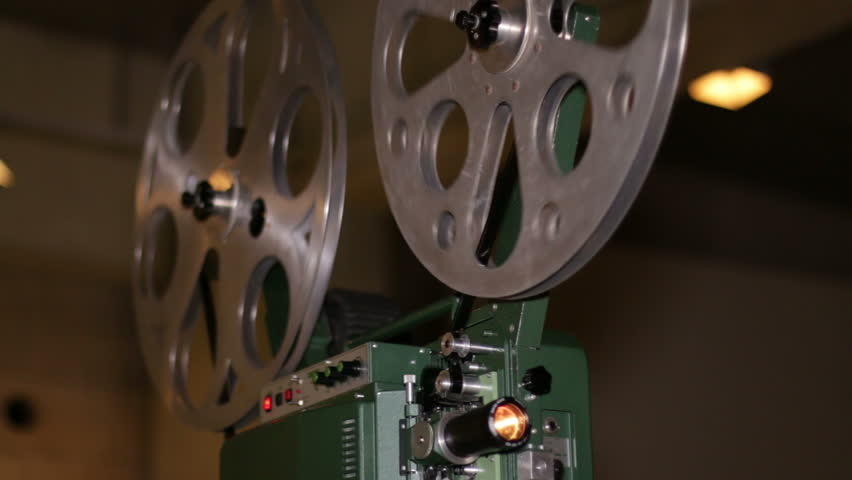 Film Projector Projecting 16mm Movie. A technician projects a 16mm film. 16mm film projection cinema technical footage. Film Technician mounting a 16mm film reel in a film festival.