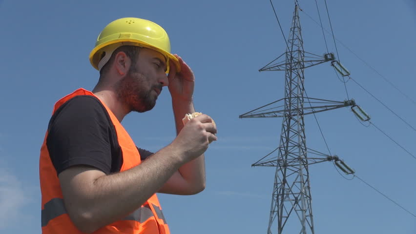 Electrician Writing On Clipboard Outside Near High Voltage Pole ...