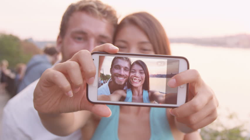 Smart phone selfie - couple taking self portrait using smartphone camera. Dating couple in love having fun taking candid fresh picture photo laughing smiling. Caucasian man, Asian woman at sunset.   Shutterstock HD Video #8454985
