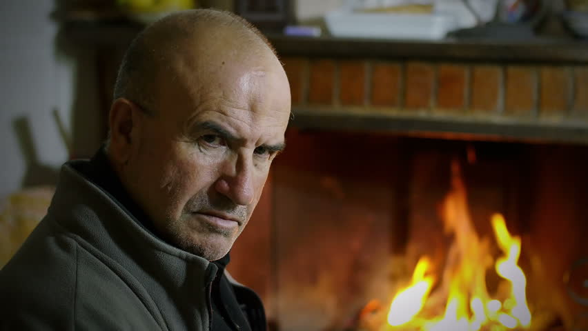 Depressed Man Portrait With Fire In Background In The Fireplace