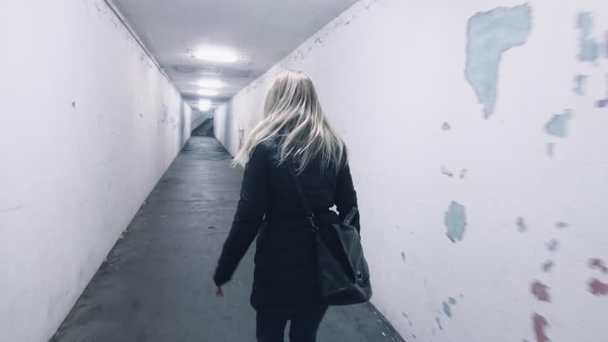 frightened scared woman in panic runs away from murdered mugger rapist bad man shaky effect back view horror dark mood uhd 4k