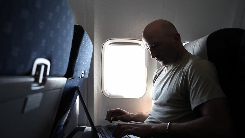 A middle-aged adult man is working with a laptop during a flight