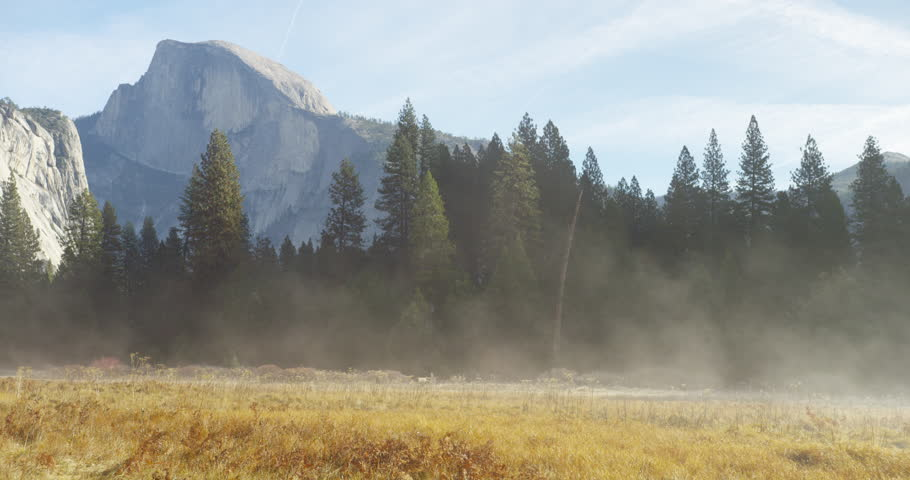 The warmth from the sun's rays melts the snow in the meadows, in turn creating a thick mist. Half Dome can be seen in the distance. Shot on Red Epic.