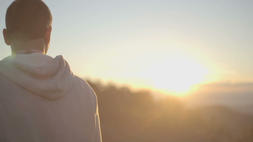 Back view of young man looking at sun in nature mountain outdoor at sunrise or sunset - HD video footage