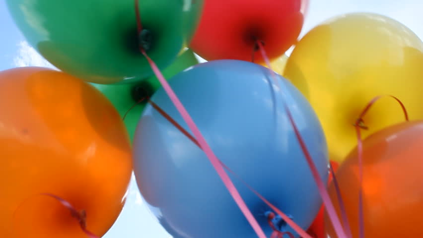 Colorful helium balloons fly up into the sky