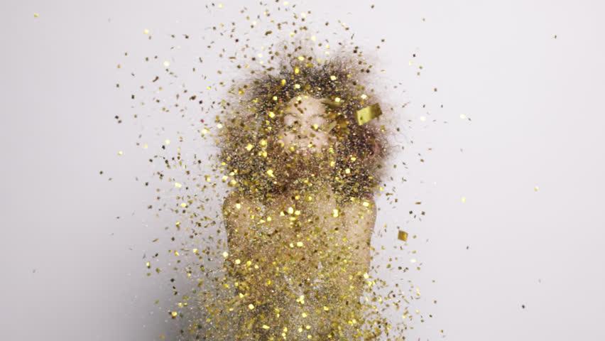Beautiful hispanic woman blowing gold glitter confetti slow motion - Red Epic Dragon