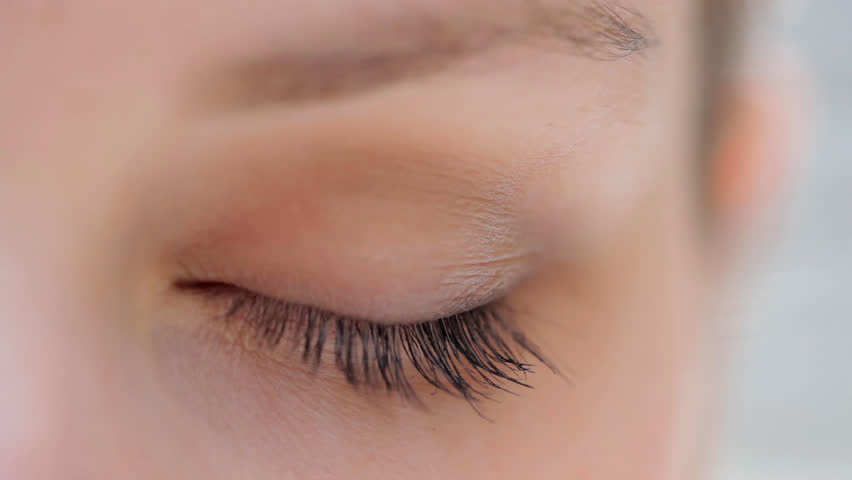 Close up detail view of a young caucasian woman eye looking at the camera and blinking slowly. Eyes and vision well being and healthy eye sight. Attractive woman with blue green eyes.